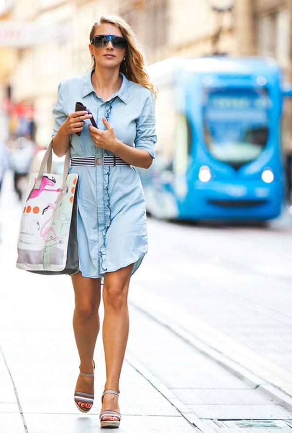 Ingin menciptakan gambar yang lebih elegan, lalu lihat lebih dekat pada gaun denim biru tua, serta sepatu perahu biru dan tas tangan bentuk persegi panjang, ...